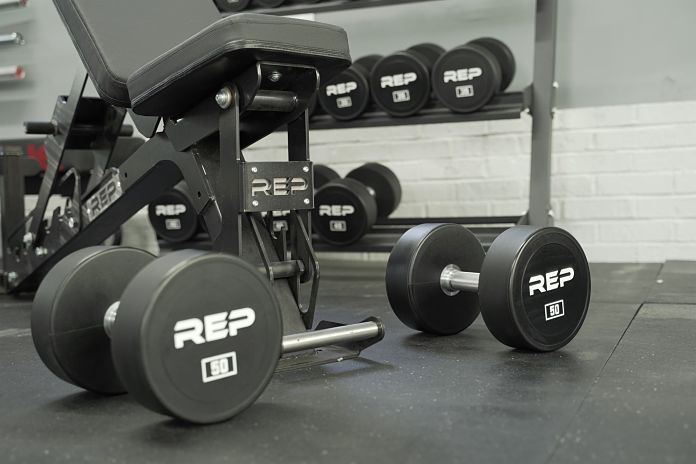 Rep Fitness AB-5200 bench with two urethane dumbbells sitting on a floor that has black horse stall mats from Tractor Supply Company