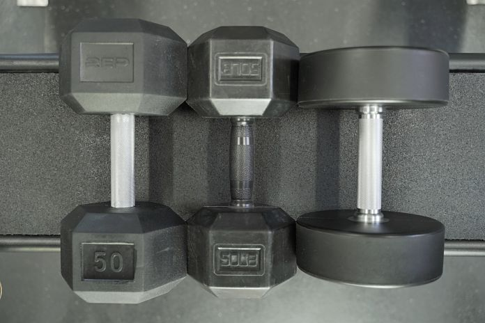 rubber hex, rubber grip, and urethane dumbbells laying next to other on a sorinex utility seat showing their relative size