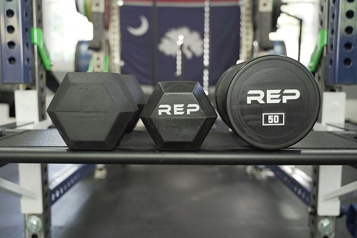three heads of the rep fitness dumbbells with rubber hex on the left, rubber grip in the middle, and urethane on the right