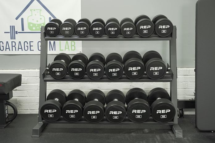 set of 5-50lb urethane dumbbells in a dumbbell rack with a garage gym lab banner behind it on the wall