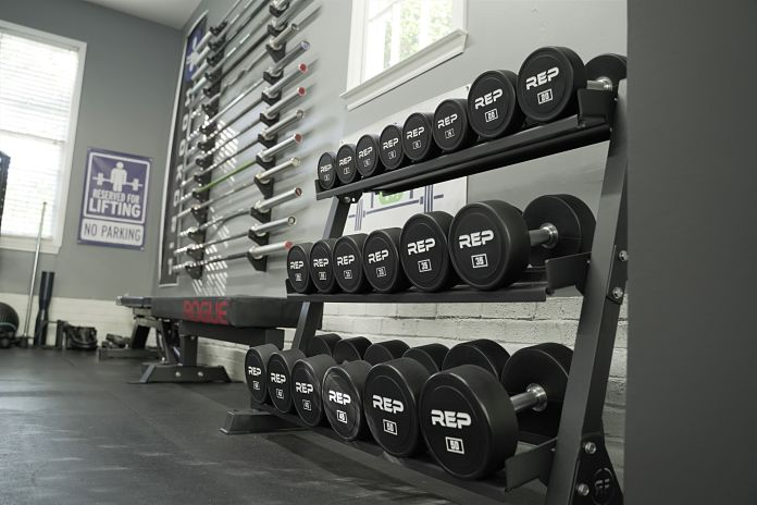 dumbbell rack from rep fitness with a 15 barbells sitting on the wall behind it as well as a reserved for lifting banner and a flat bench with a Thompson Fat Pad