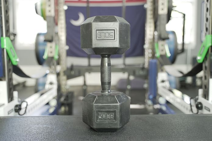 front view of a Rep Fitness rubber grip dumbbell standing on a utility seat
