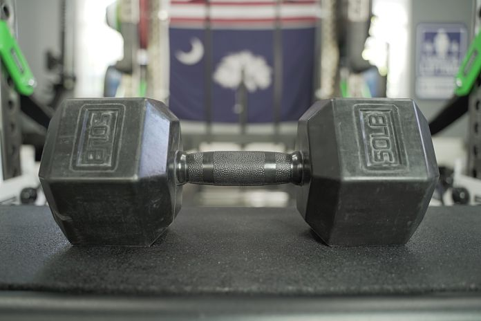 Rubber grip dumbbell from laying on side showing the weight label of 50 lbs