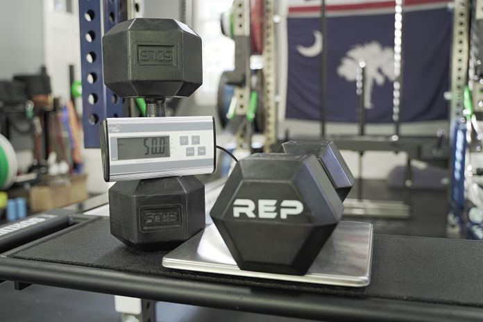 Rubber grip dumbbell on scale showing a perfect weight of 50 lbs with Rep at end
