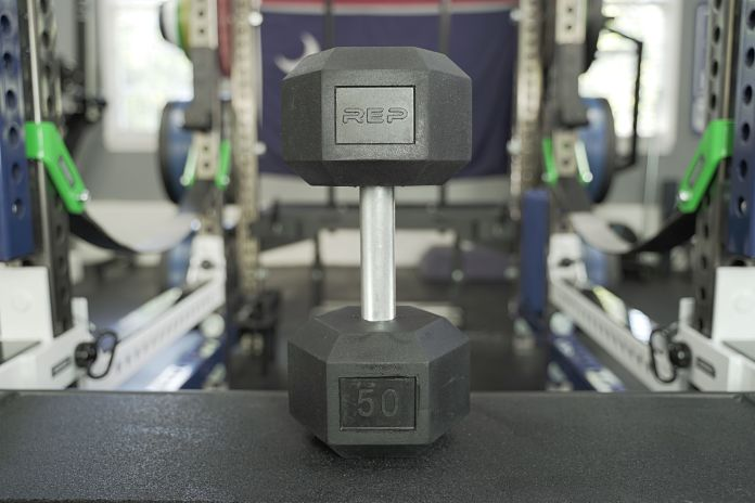Rep Fitness Rubber Hex Dumbbell ttanding tall on a utility bench showing height and the overall profile