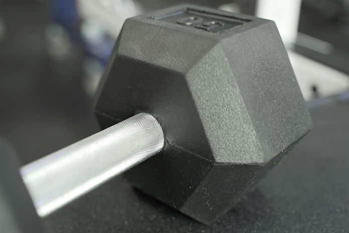 Rubber Hex dumbbell showing friction welded head and knurling on handle