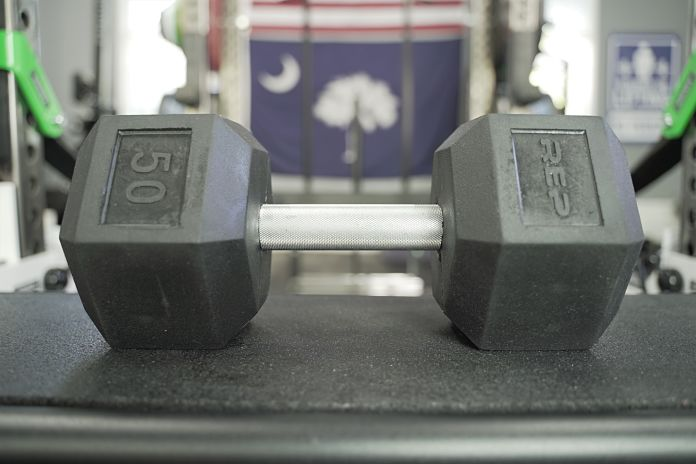 Rubber hex dumbbell on side showing Rep label and 50 pound marker