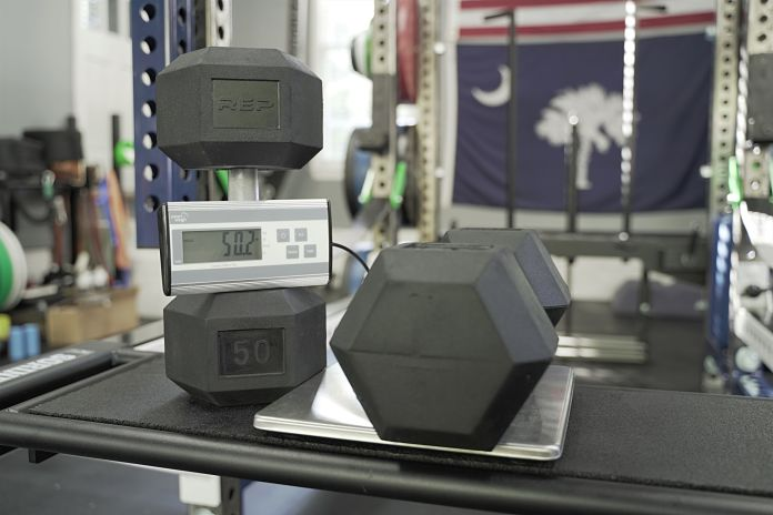 Rep rubber hex dumbbell on scale showing weight of 50.2 lbs