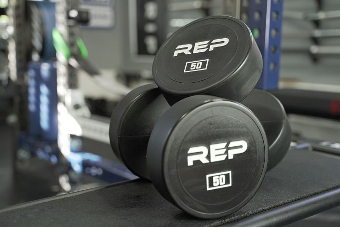 Urethane dumbbells from Rep Fitness laying on side with Sorinex rack in background