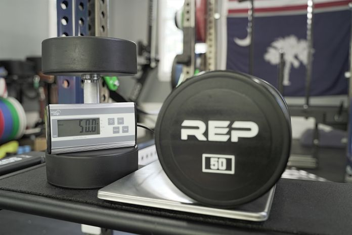 Urethane dumbbell from rep sitting on a scale showing a perfect weight of 50 lbs with the South Carolina state flag in background