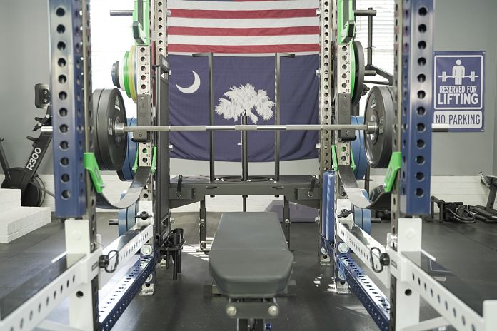 front view of the bar being used for bench press with a Zero Gap bench inside a Sorinex Rack