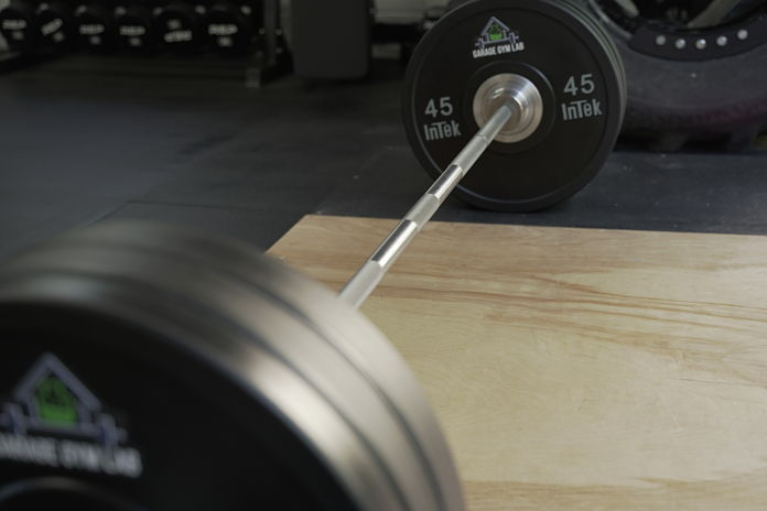 Stainless steel shaft of the bar sitting on a homemade deadlift platform