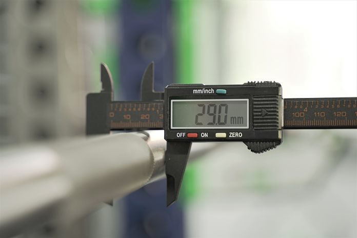digital calipers around the shaft of barbell the showing a diameter of 29 millimeters