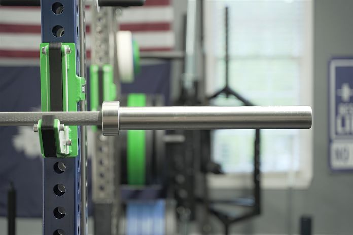 The stainless steel powerlifting barbell sits in a Sorinex Rack on green custom j-cups in order to show the sleeves are smooth and fully stainless steel