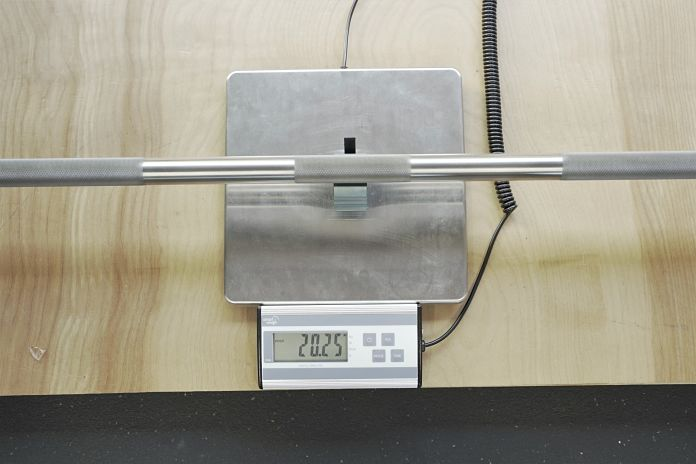 the stainless steel aggressive powerlifting barbell from rep is sitting on a digital scale showing a weight of 20.25 kilograms