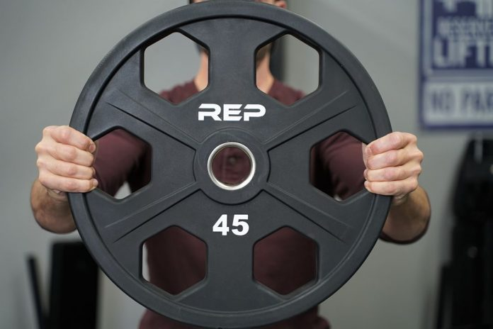 Rep Urethane Equalizer Plates being held in hands - Garage Gym Lab